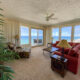 view of living room and large windows looking over the beach and Gulf